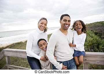 Happy African-American family of four on beach - Happy...