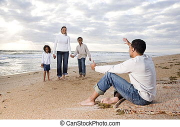 Happy African-American family of four on beach
