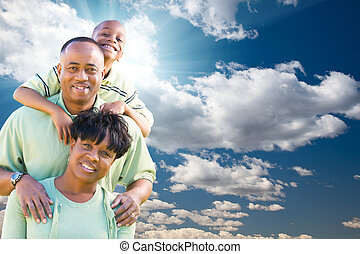 Happy African American Family Over Blue Sky and Clouds