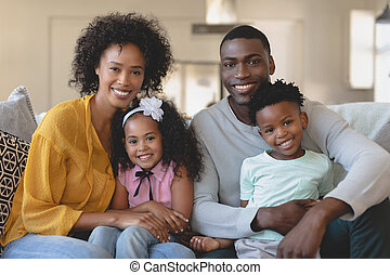 Happy African American family sitting on sofa and looking at...