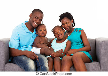 African American family sitting on sofa