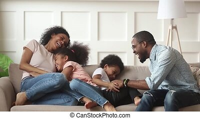 Happy african american family with kids laugh tickle at home