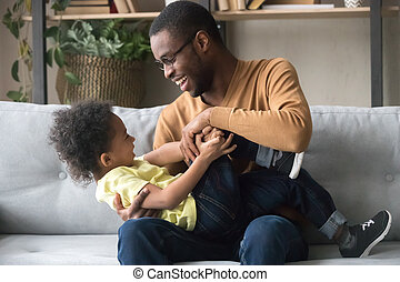 Happy African American father playing with toddler son at home