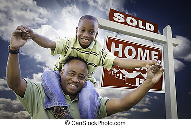 Happy African American Father with Son In Front of Sold Home...