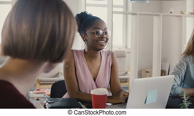 Happy African American female employee sitting by the table at team meeting. Multiethnic teamwork in modern office 4K.