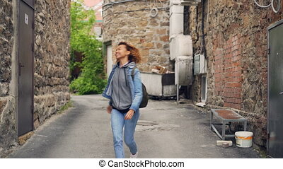 Happy African American girl glad tourist with backpack is...