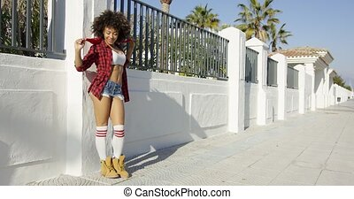 Happy african american girl leaning on fence. She wearing...