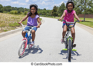 Happy African American Girls Riding Bikes