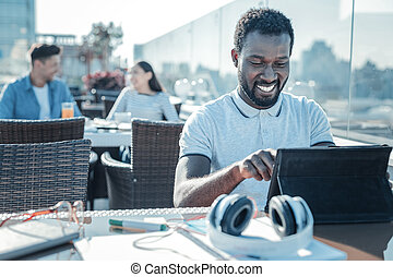 Happy african american grinning broadly while using touchpad