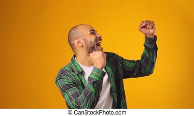 Happy african american man celebrating success against yellow background. High quality FullHD footage