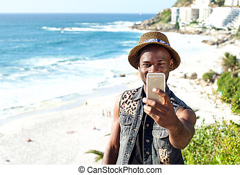 Happy african american man on vacation taking selfie
