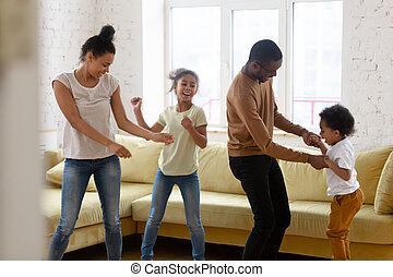 Happy african american mother and father with two children dancing.
