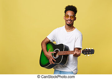 Happy african american musician man posing with a guitar, over golden yellow background.