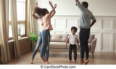 Happy african american parents and cute kids dancing at home