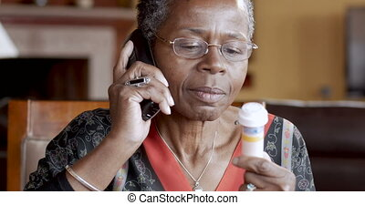 Happy African American senior woman calling in her prescription to pharmacy