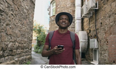 Happy african american student walking and using smartphone...