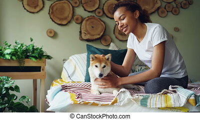 Happy African American teenage girl is caressing pet dog...