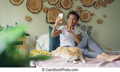 Happy African American teenager is making video call with smartphone calling friends talking and gesturing while her cute dog is lying on bed with her.
