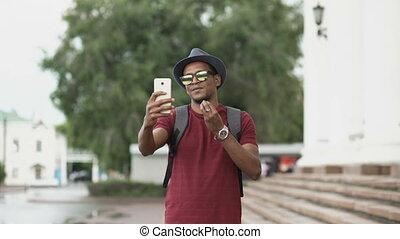 Happy african american tourist man having online video chat using his smartphone camera while travelling in Europe