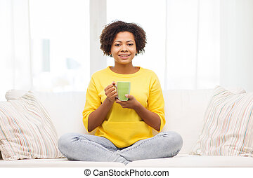 happy african american woman drinking from tea cup