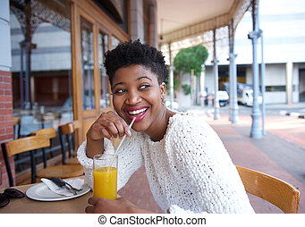 Happy african american woman drinking orange juice