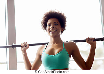 happy african american woman holding bar in gym