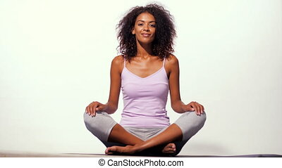 Happy african american woman in comfortable sports wear meditating on mat over white wall background. Black girl concentrated on yoga practice.