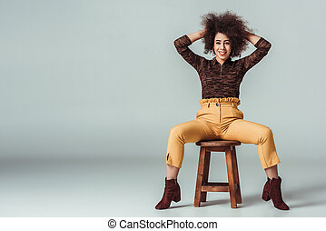 happy african american woman in retro clothes sitting on chair and looking at camera on grey