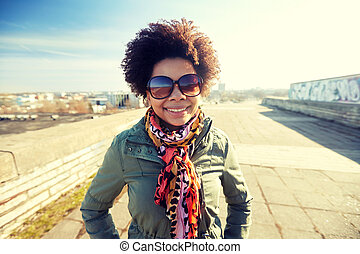happy african american woman in shades on street - tourism,...
