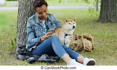 Happy African American woman is using smartphone and...