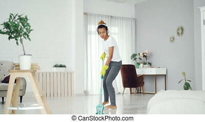 Happy African American woman is washing floor with plastic mop, singing and dancing listening to music through headphones. People and technology concept.