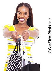 african american woman offering shopping bags