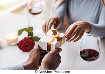 Happy African American woman opening the box from her boyfriend