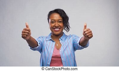 happy african american woman showing thumbs up - gesture and...