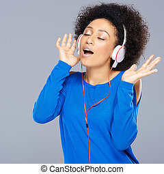 Happy African American woman singing to music