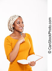 Happy african american woman smiling and writing in notebook