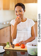 african american woman tasting tomato