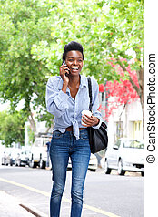 happy african american woman walking on street with cell phone