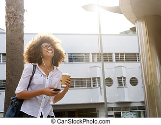 Happy african american woman walking with cellphone