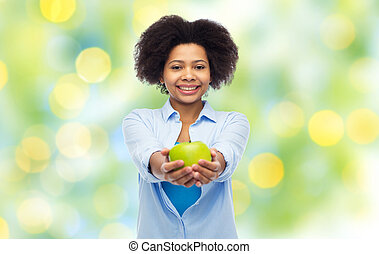 happy african american woman with green apple