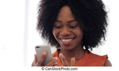 happy african american woman with smartphone - technology...