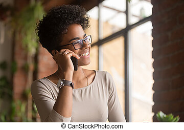 Happy african american young businesswoman talking on phone in office