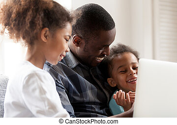 Happy African American young family watch cartoons on laptop