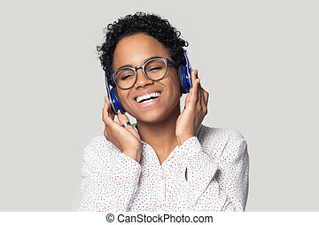 Happy african american young girl listening to favorite music.