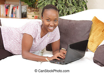 Happy African American young woman using a laptop