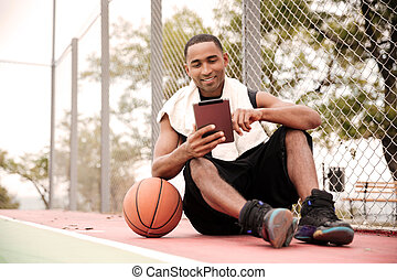 Happy african basketball player sitting in park and using tablet