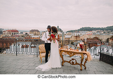 Happy african bride and groom happily hugging on the terrace