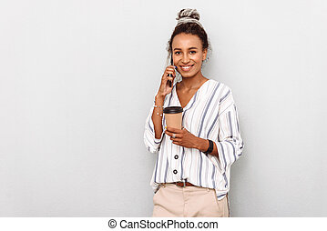 Happy african business woman with dreads isolated over white wall background drinking coffee talking by mobile phone.