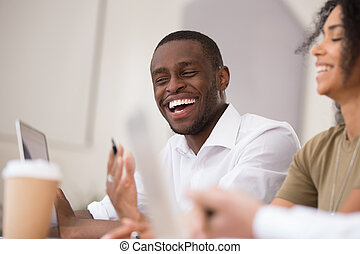Happy african businessman laughing talking working together with friendly colleagues
