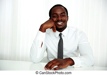 Happy african businessman sitting at the table in office